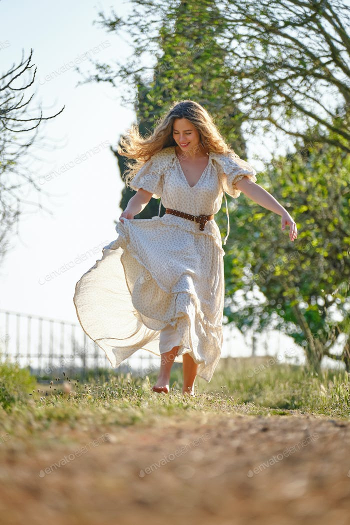 Cheerful woman running in garden