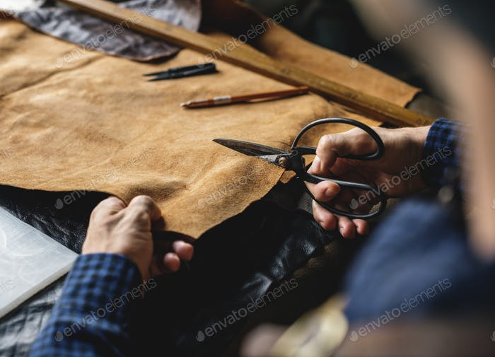 Closeup of craftsman cutting leather handicraft