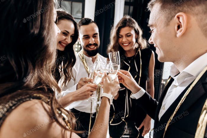 Company of happy friends dressed in stylish elegant clothes stand together and clink glasses with