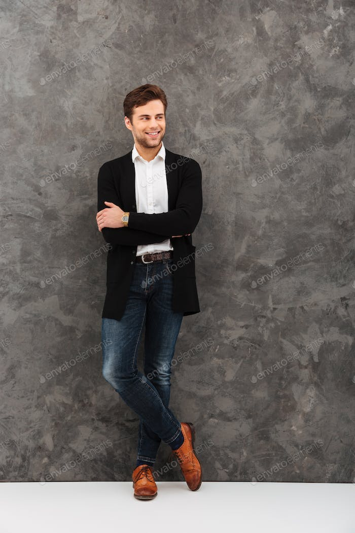 Cheerful young businessman standing over grey wall