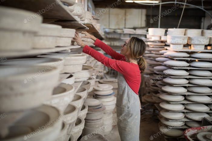 Female potter placing craft product in shelf