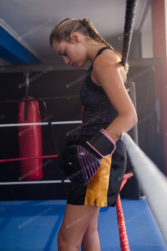 Thoughtful woman standing in boxing ring