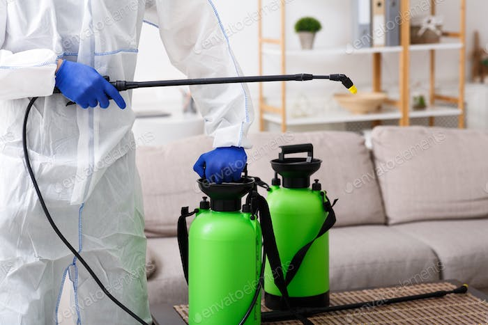 Unrecognizable person disinfecting home sofa with cleaning spray