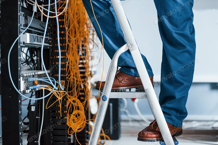 Man in uniform stands on the ladder and works with internet equipment and wires in server room