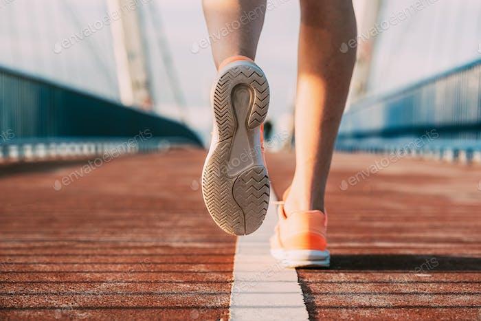 crop woman running on the bridge