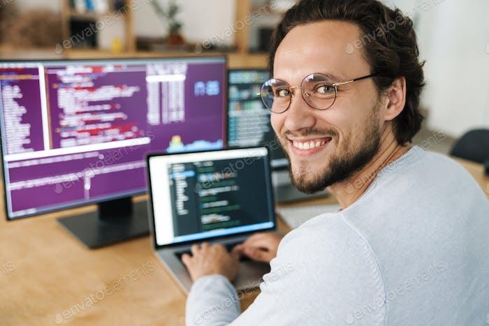 Imagen del hombre programador usando anteojos trabajando con computadoras