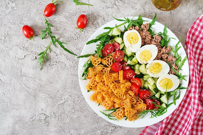 Pasta salad with fresh vegetables, eggs and tuna in a white bowl.
