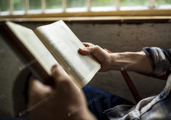 Closeup of hands holding reading book