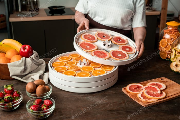 Housewife putting dryer tray with sliced grapefruit on that with orange slices