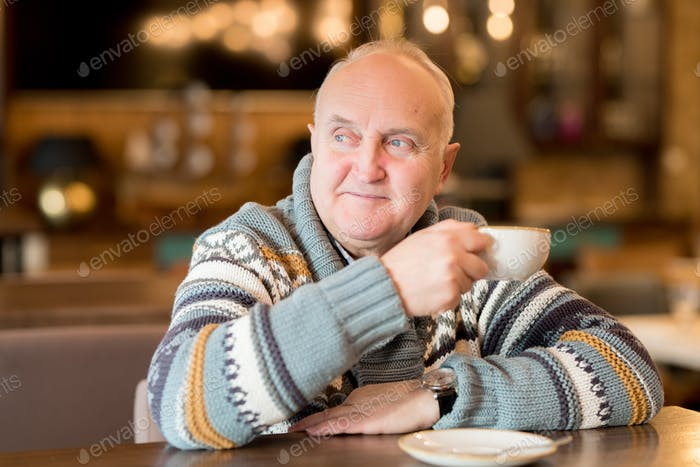 Chubby man in sweater sitting in cafe
