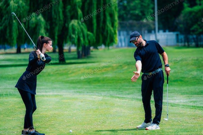 Golf spielen. Junge Frau spielen Golf mit Golf-Instruktor