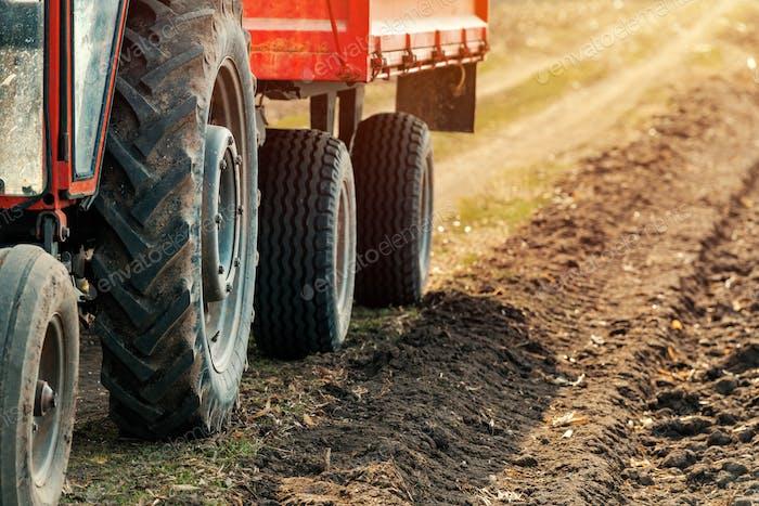 Alte rote landwirtschaftliche Traktor mit Anhänger auf unbefestigte Landschaft