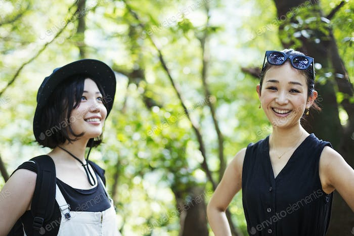 Two smiling young women standing in a forest.