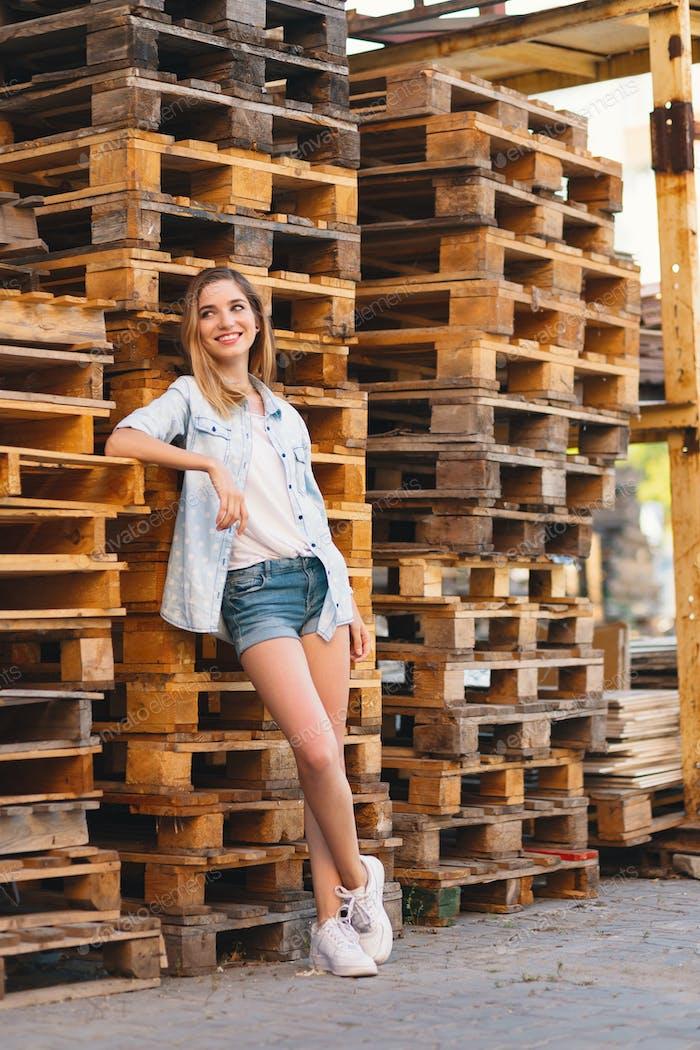 Chica muy sonriente, usando jeans, pantalones cortos y camisa posando sobre Fondo de madera