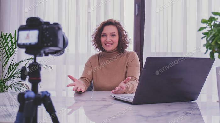 Adult woman speaks in front of a video camera for her blog channel.