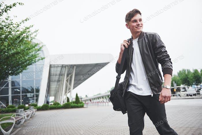 Junge gutaussehende Mann mit einer Tasche auf der Schulter in Eile zum Flughafen