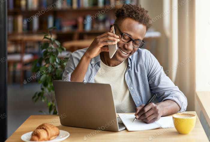 Joyful black guy talking on smartphone while studying online at coffee shop