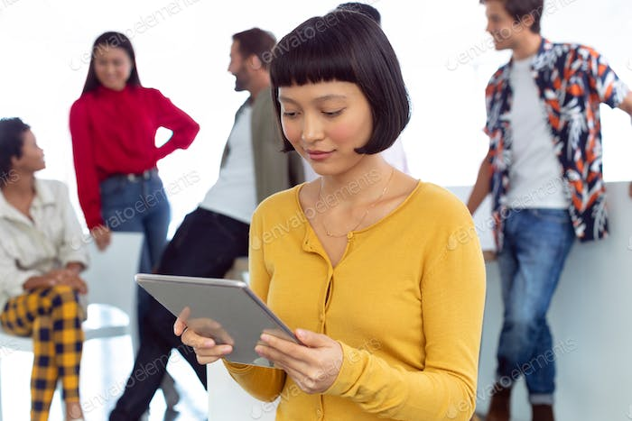 Front view of young Asian businesswoman working on digital tablet in a modern office