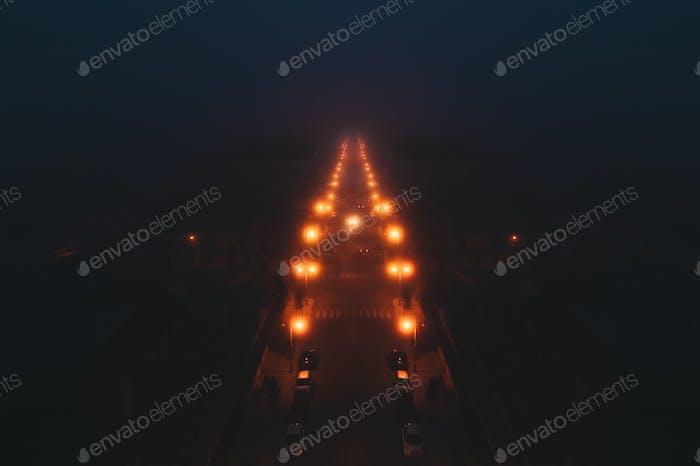 Carretera iluminada por faroles envueltos en niebla