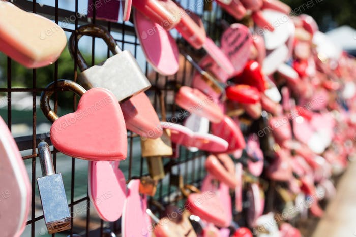 Closeup on pink love locks hanging with space for copy