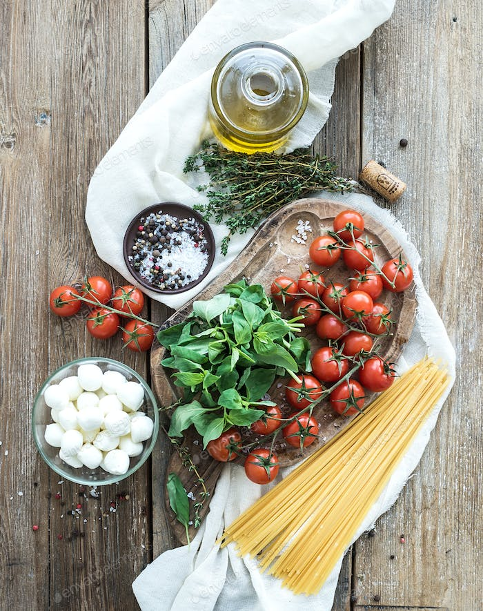 Ingredients for cooking pasta. Spaghetti, basil, cherry-tomatoes, mozarella, olive oil