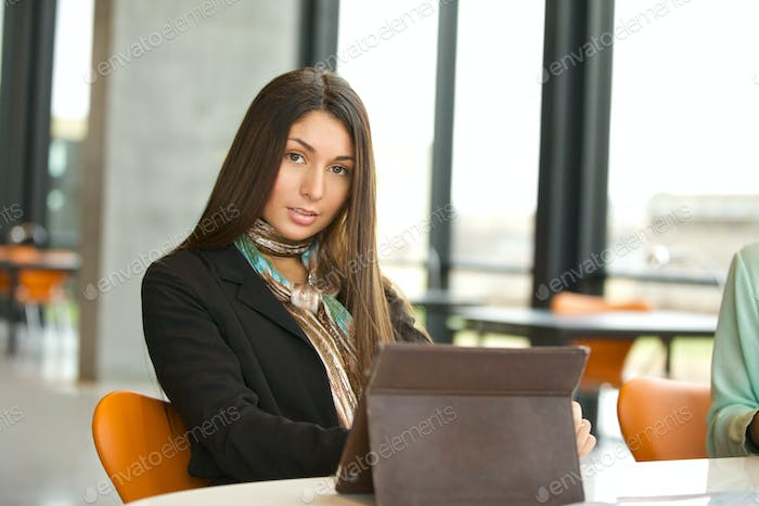 Young female student at library with digital tablet