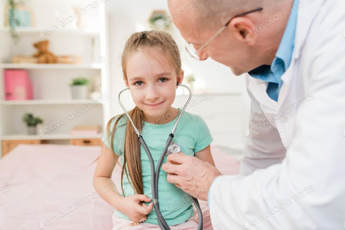 Smiling little girl with stethoscope listening to her heartbeat