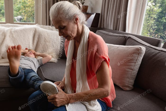 Side view of Caucasian grandmother removing shoes of her grandson on sofa in a comfortable home
