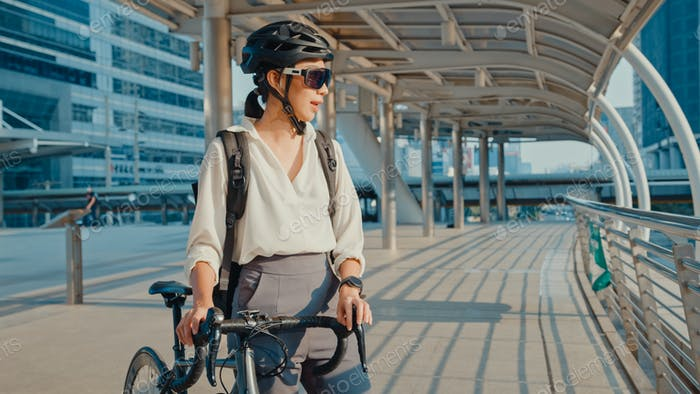 Asian lady go to work at office walk and smile look around hold bicycle stand around building.
