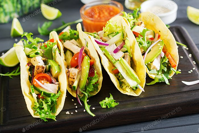 Mexikanische Tacos mit Hühnerfleisch, Avocado, Tomaten, Gurken und roten Zwiebeln.