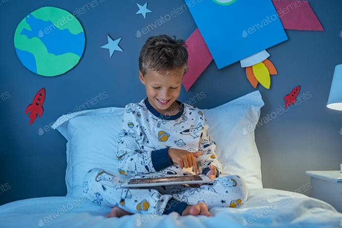 Kid watching galaxies on tablet during night