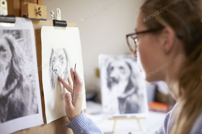 Side View Of Female Teenage Artist Sitting At Easel Drawing Picture Of Dog From Photograph