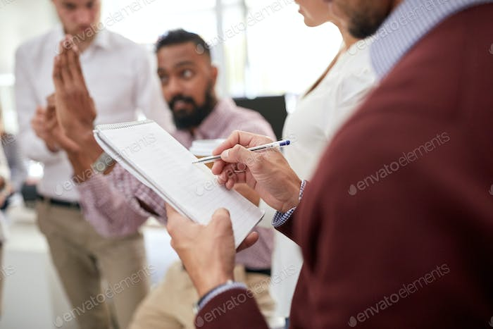 business team and man writing to notepad at office