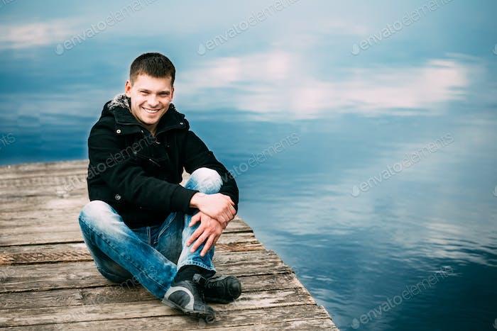 Junge kaukasische gutaussehende Mann sitzend auf Holz pier im Frühjahr oder