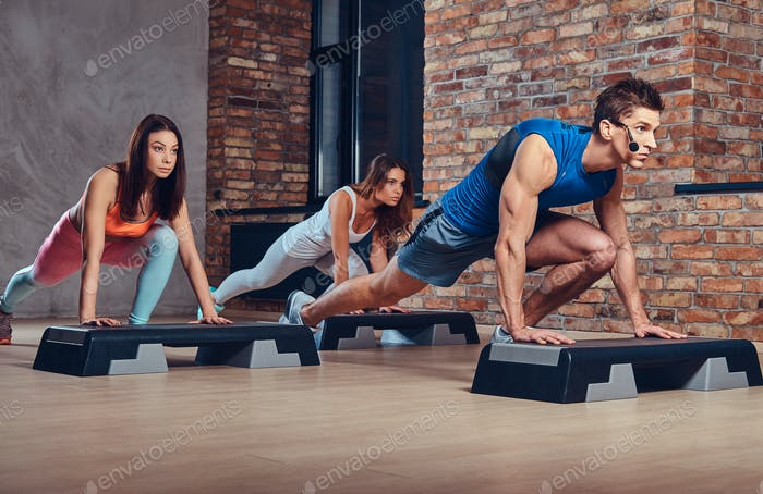 A man learning women how to do push ups.