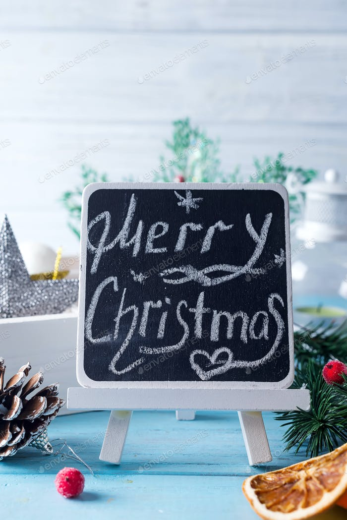 """Black chalkboard with caption """"Merry Christmas!"""" and christmas decoration on blue"""