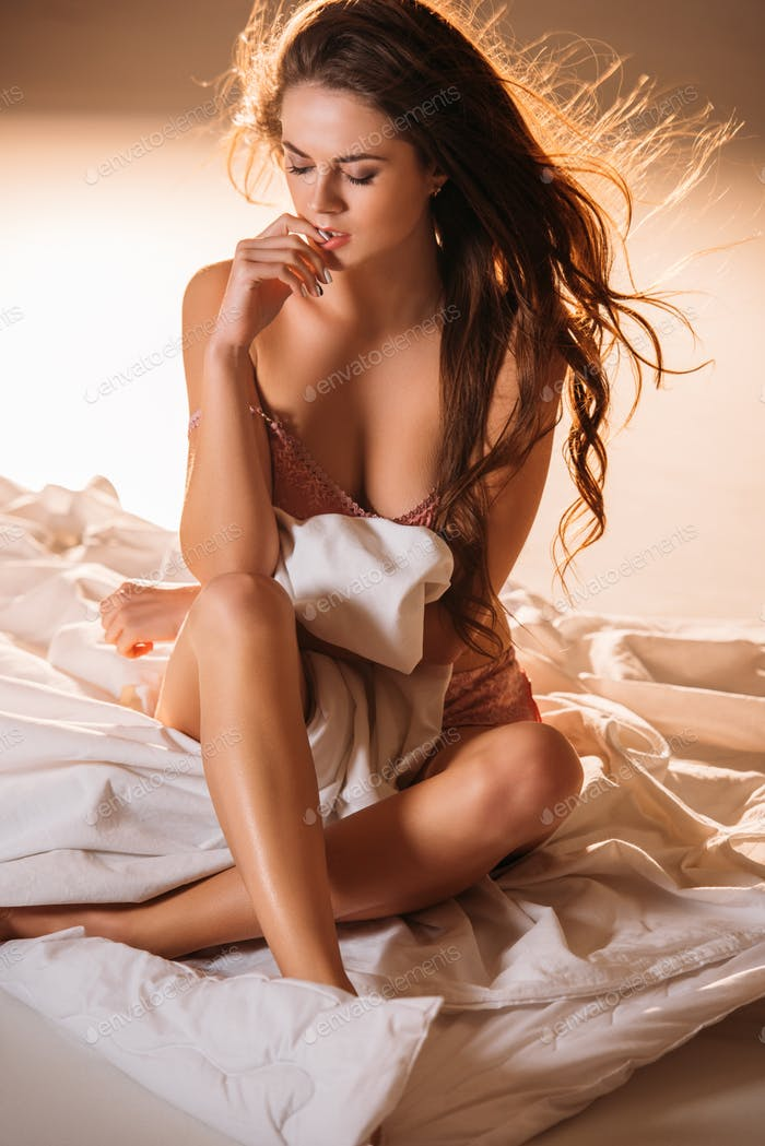 sexy girl with closed eyes covering body with blanket