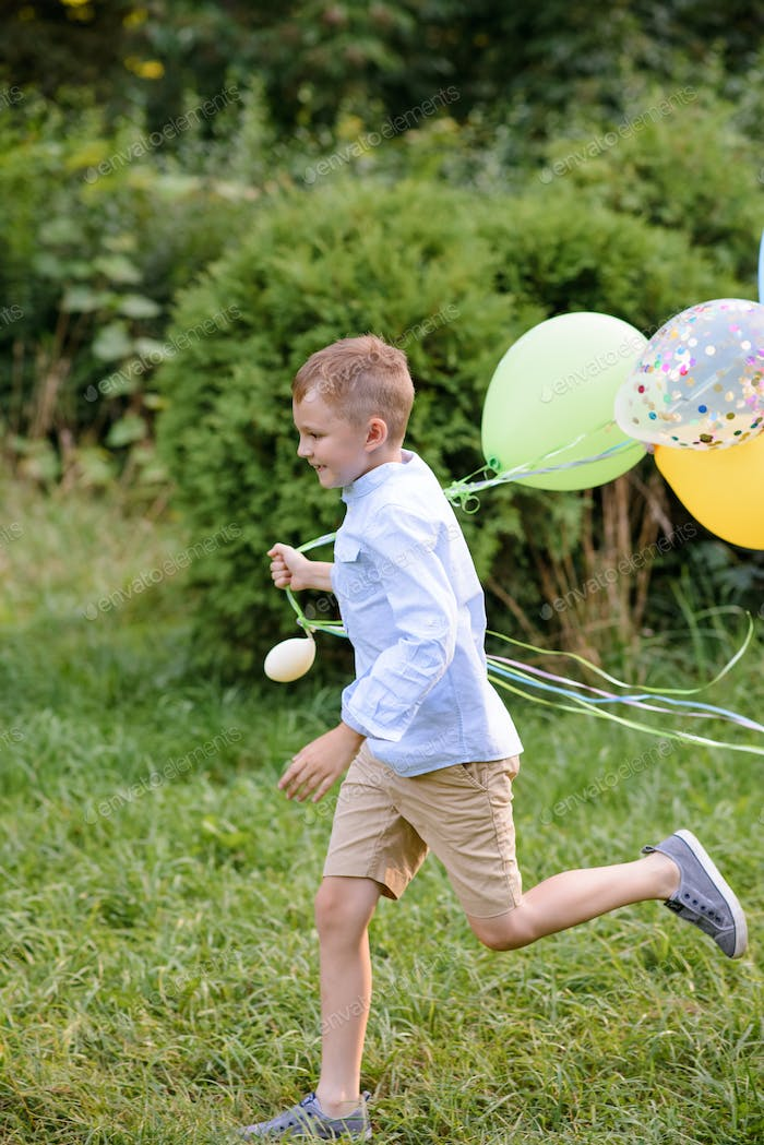 A boy of primary school age runs with balloons. The boy celebrates his birthday in the park.