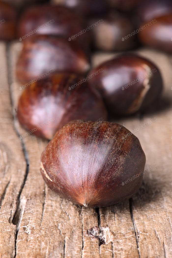bunch of chestnuts ready to be roasted on rustic wood