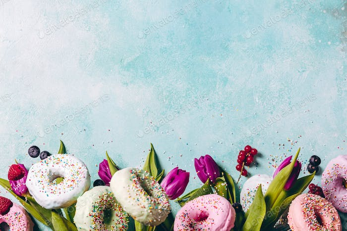 Sweet and colourful doughnuts with sprinkles, purple tulips and