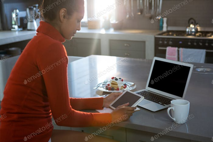 Woman using tablet at kitchen counter