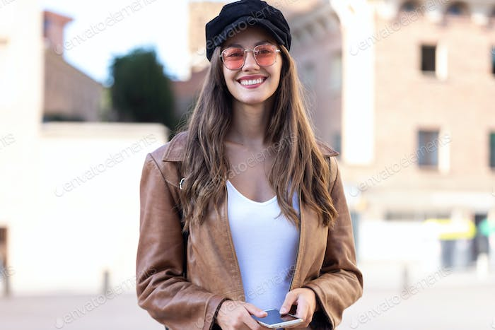 Pretty young woman looking at camera while holding mobile phone and standing in the street.