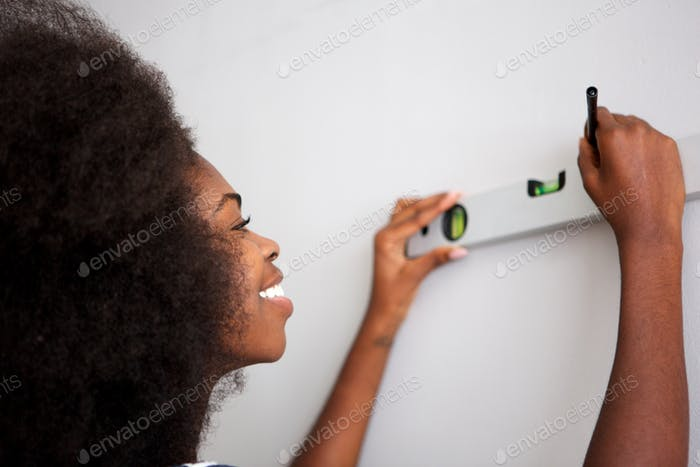 Close up happy young black woman drawing straight line on wall