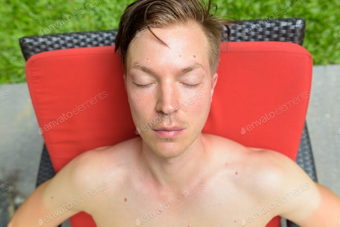 Young handsome man relaxing by swimming pool in hotel at Kuala L