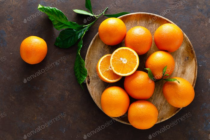 Oranges with leaves on dark background, top view