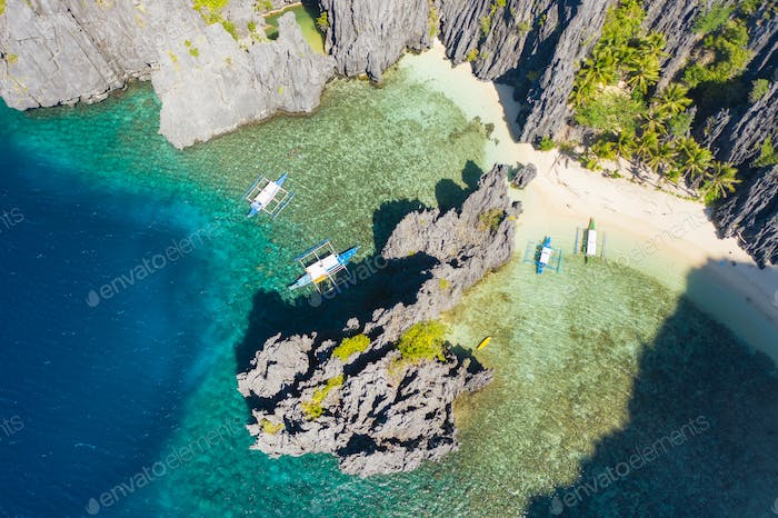 El Nido, Palawan, Philippines, aerial view of boats in lagoon and cliffs rocky mountains scenery at