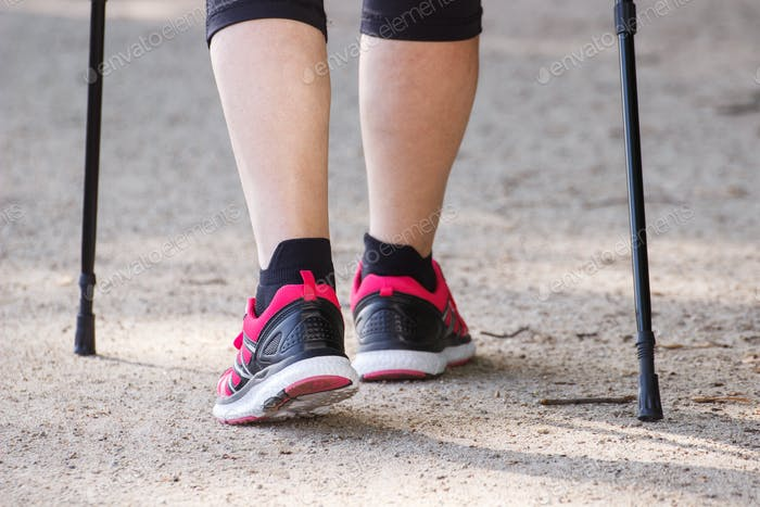 Legs of elderly senior woman practicing nordic walking, sporty lifestyles in old age concept