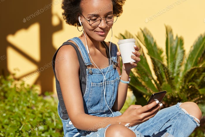 Cropped image of hipster girl with Afro haircut, enjoys takeout coffee, wears ripped jean overalls,
