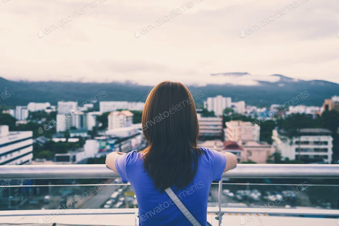 Hipster young girl looking the city on observation deck