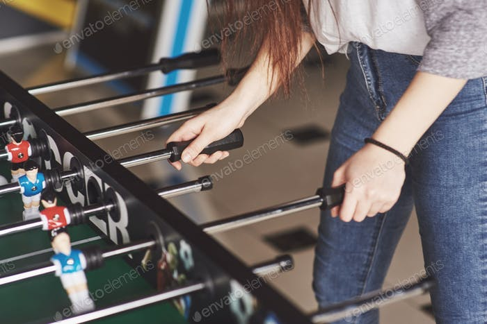 Table football in the entertainment center. Beautiful girl playing football